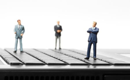 statuette: Miniature figurines of successful businessman and team standing on laptop keyboard Stock Photo