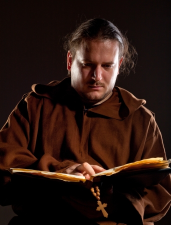 Portrait of pensive monk reading the bible photo