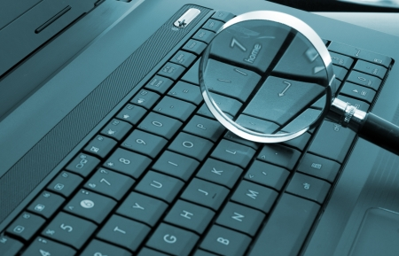 Magnifying glass on laptop computer. Toned in blue Stock Photo - 18192603