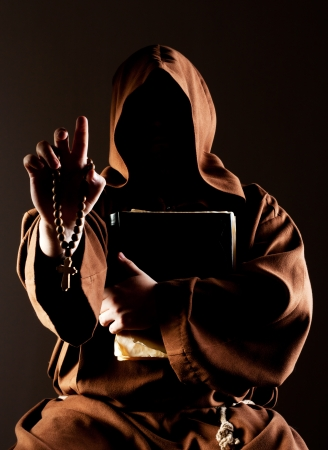 Portrait of mystery preaching monk with wooden rosary and bible photo