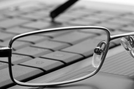 Businessmans glasses on laptop computer photo