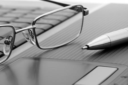 Businessmans glasses and pen on laptop computer photo