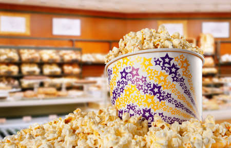 popcorn bowls: Shot of popcorn in large bucket against shop interior Stock Photo