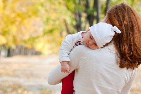 Sleeping little girl on mothers shoulder in autumn park Stock Photo