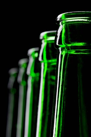 Row of open green beer bottles. Close-up view photo