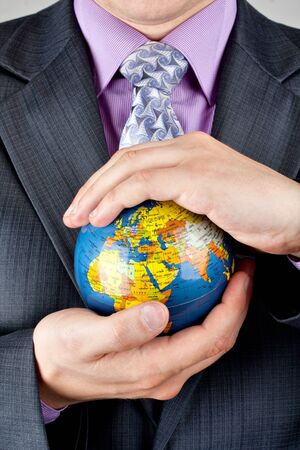 Close-up of a businessman carrying world globe Stock Photo - 18289026