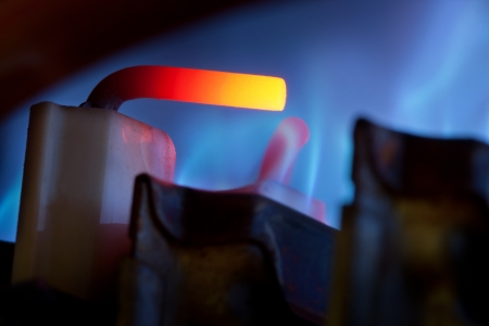 firebox: Close-up view of gas control and blue flames in gas boiler