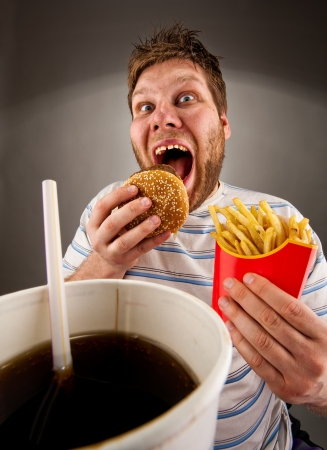 man eten: Portret van expressieve man het eten van fast food