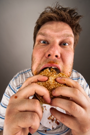 ugly mouth: Portrait of expressive fat man chewing hamburger