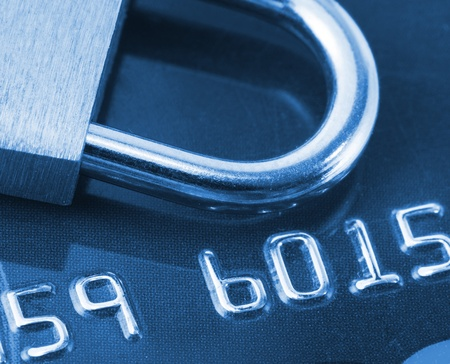 Close-up view of credit card and padlock. Toned in blue photo
