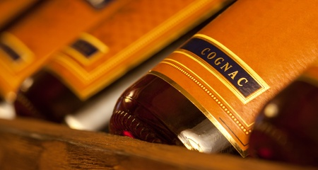 whiskey bottle: Row of wealth cognac bottles in cellar