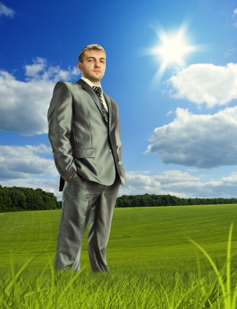 businessman standing: Confident businessman standing on meadow in beautiful day