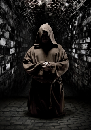 Mystery monk praying on kneels in dark temple corridor