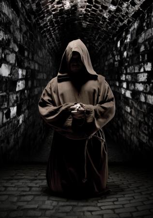 cassock: Mystery monk praying on kneels in dark temple corridor