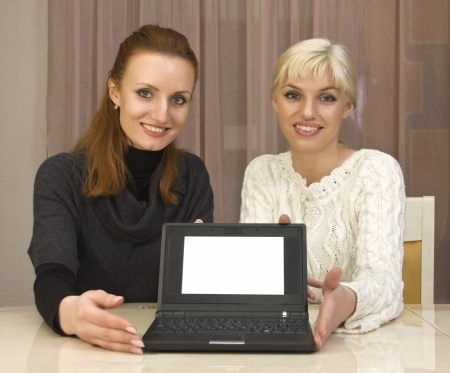 Two businesswomans showing a sign on laptop photo