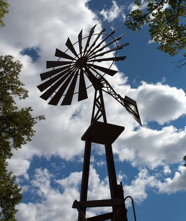 Silhouette of old-fashioned farm windmill photo