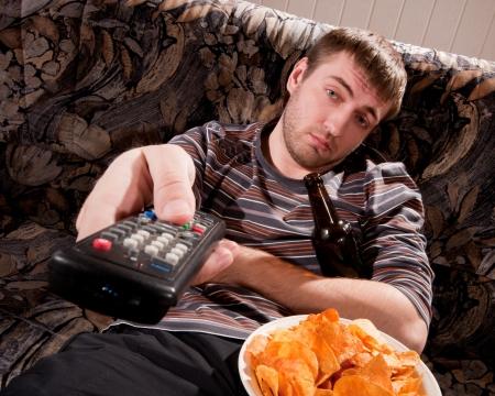 Hombre so�oliento con la cerveza y patatas fritas viendo la televisi�n en casa Foto de archivo