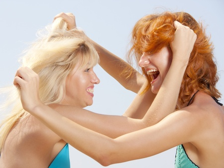 pull out: Two aggressive women in bikini pulling out hair each other Stock Photo