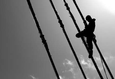 Silhouette of construction climber on suspension bridge photo