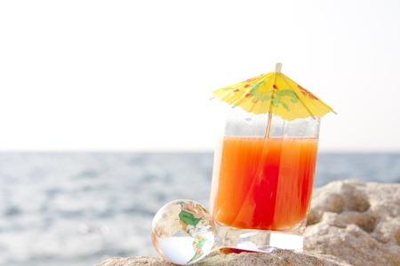 Cocktail and glass globe by the sea photo