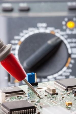 service engineer: Probe of digital multimeter analyzing electronics circuit