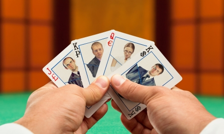 Businessmen playing poker with business team cards Stock Photo - 18303811