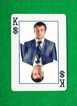Confident businessman on king of dollars gambling card photo