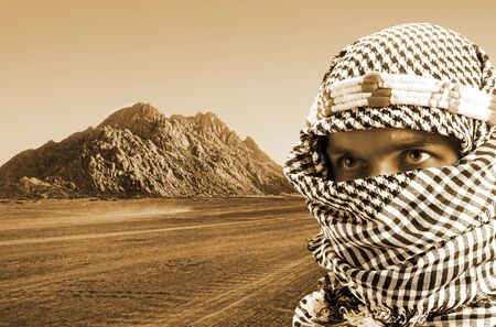 middle eastern ethnicity: Portrait of serious middle eastern man in desert at sunset. Sepia toned