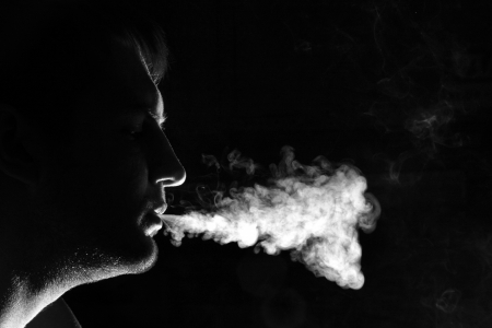 Silhouette of smoker exhales smoke photo