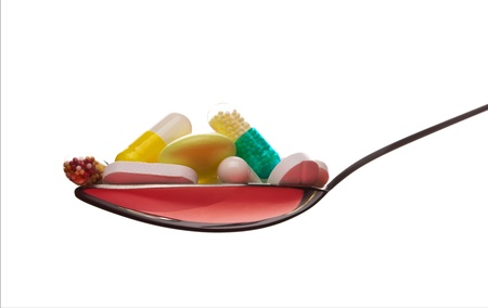 Spoon full of various pills. Isolated on white Stock Photo - 18312133