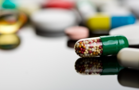 Closeup of capsule against various colorful pills on background photo