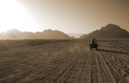 rough road: Four wheel motorbike rally in desert Stock Photo