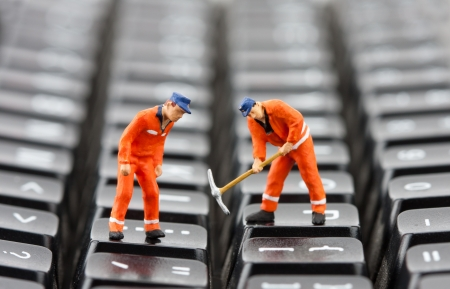 Small figurines of workers repairing computer keyboard Stock Photo - 18312350