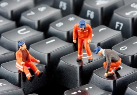 computer repairing: Small figurines of workers repairing computer keyboard Stock Photo