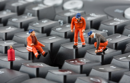 computer problems: Small figurines of workers repairing computer keyboard Stock Photo