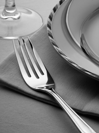 Dinner set with fork, plate and napkin on the table photo