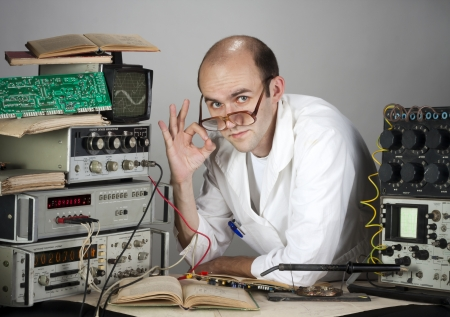 Pensive scientist working at vintage technological laboratory. Showing OK sign photo