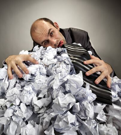 depressive: Exhausted depressive businessman laying on big heap of crumpled papers Stock Photo