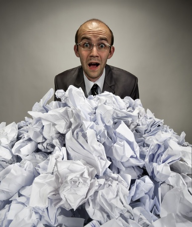 Surprised businessman reaches out from big heap of crumpled papers photo