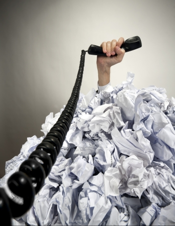 Hand with phone reaches out from big heap of crumpled papers photo