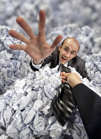 office chaos: Helping hand saving businessman buried in big heap of crumpled papers