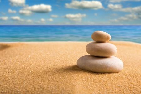 Macro de trois jalonnés de pierres zen sur la plage