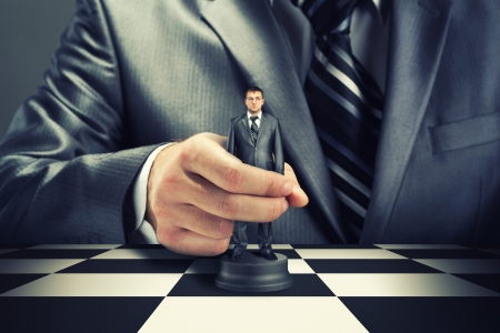 winning idea: Big boss playing chess using businessman Stock Photo