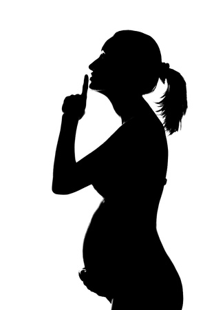 female nudity: Silhouette of pregnant woman holding abdomen and showing SHH sign