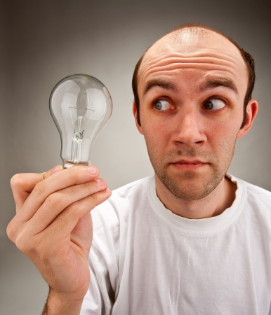 afflatus: Waiting for idea... Man holding electrical bulb Stock Photo