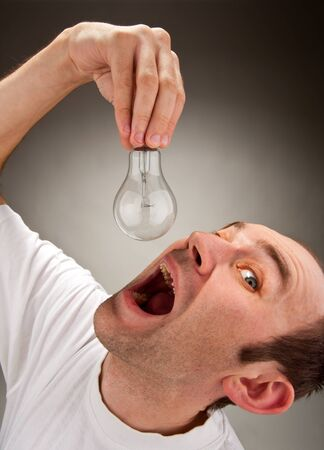 afflatus: Absorption ideas. Man trying to eat electrical bulb