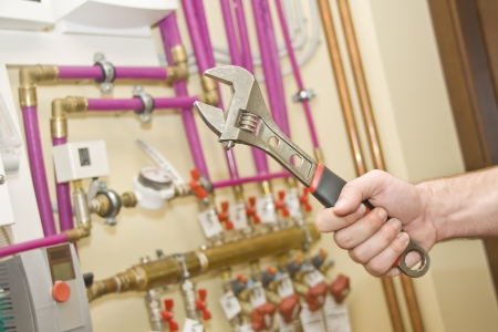 Servicing heating and water systems. Hand with adjustable spanner Stock Photo - 18312609