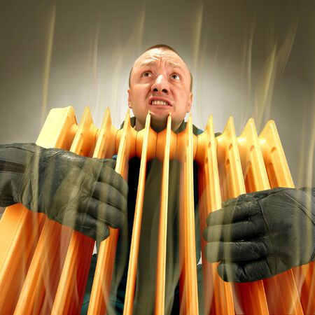 freezing: Bizarre freezing man holding hot oil radiator Stock Photo