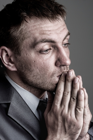 job loss: Portrait of sad praying businessman looking for solutions