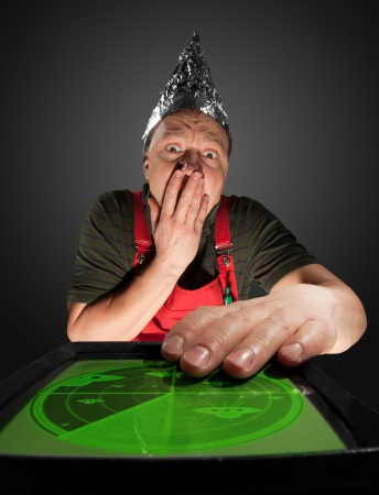 Scared man wearing a foil hat and watching old radar monitor with ufo Stock Photo - 18341963